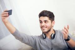 Ηλικίας σπουδαστής αρσενικό που παίρνει ένα selfie με το τηλέφωνό του στο σπίτι Στοκ Φωτογραφίες