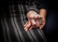 Ηλικίας χέρι που κρατά το νέο χέρι Στοκ Φωτογραφίες