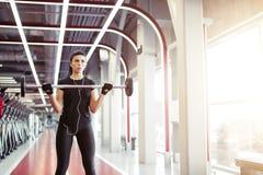 Η ικανότητα, κλείνει επάνω της νέας γυναίκας παίρνει για τους δικέφαλους μυς στη γυμναστική Στοκ Εικόνες