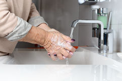Ηλικιωμένα χέρια πλύσης γυναικών κάτω από τη βρύση Στοκ φωτογραφία με δικαίωμα ελεύθερης χρήσης