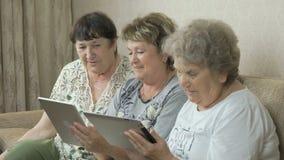 Ηλικιωμένες γυναίκες που κρατούν τις ψηφιακές ταμπλέτες φιλμ μικρού μήκους