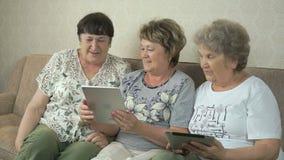 Ηλικιωμένες γυναίκες που κρατούν τις ψηφιακές ταμπλέτες απόθεμα βίντεο