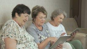 Ηλικιωμένες γυναίκες που φαίνονται φωτογραφίες που χρησιμοποιούν τις ψηφιακές ταμπλέτες απόθεμα βίντεο