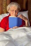 Ηλικιωμένη ανάγνωση γυναικών στο κρεβάτι στοκ εικόνες