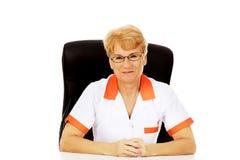 Ηλικιωμένη γιατρός ή νοσοκόμα θηλυκών χαμόγελου στα γυαλιά που κάθεται πίσω από το γραφείο Στοκ φωτογραφία με δικαίωμα ελεύθερης χρήσης