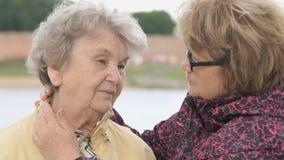 Ηλικιωμένη γυναίκα γυναικών soothes κατά τη διάρκεια της πίεσης υπαίθρια φιλμ μικρού μήκους