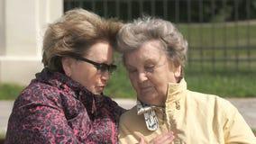 Ηλικιωμένη γυναίκα γυναικών soothes κατά τη διάρκεια της πίεσης υπαίθρια απόθεμα βίντεο
