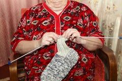 Ηλικιωμένη γυναίκα και πλέκοντας ενδύματα Στοκ φωτογραφία με δικαίωμα ελεύθερης χρήσης