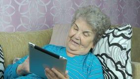 Ηλικιωμένη γυναίκα με έναν υπολογιστή ταμπλετών απόθεμα βίντεο
