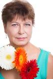 Ηλικιωμένη γυναίκα με τα gerberas στοκ εικόνα