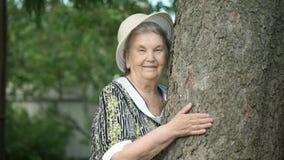 Ηλικιωμένη γυναίκα που αγκαλιάζει τα χαμόγελα δέντρων για τη κάμερα απόθεμα βίντεο