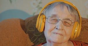 Ηλικιωμένη γυναίκα που ακούει τη μουσική στα ακουστικά απόθεμα βίντεο