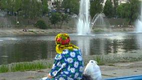 Ηλικιωμένη γυναίκα που εξετάζει την πηγή στο πάρκο κοντά στο κανάλι ποταμών πόλεων απόθεμα βίντεο