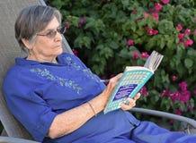 Ηλικιωμένη γυναίκα που διαβάζει ένα βιβλίο στον εγχώριο κήπο της στοκ εικόνα με δικαίωμα ελεύθερης χρήσης