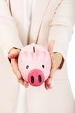Ηλικιωμένη γυναίκα που κρατά τη piggy τράπεζα Στοκ Φωτογραφία