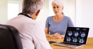 Ηλικιωμένη γυναίκα που μιλά με τον προσωπικό γιατρό για τις ανησυχίες υγείας της στοκ εικόνες