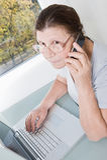 Ηλικιωμένη γυναίκα που μιλά σε ένα τηλέφωνο κυττάρων εργαζόμενη στο compu Στοκ Εικόνα