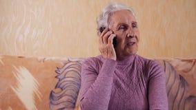 Ηλικιωμένη γυναίκα που μιλά σε ένα τηλέφωνο κυττάρων καθμένος σε έναν καναπέ Επικοινωνεί με κινητό τηλέφωνο, smartphone απόθεμα βίντεο