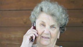 Ηλικιωμένη γυναίκα που μιλά στο τηλέφωνο κυττάρων απόθεμα βίντεο