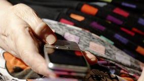 Ηλικιωμένη γυναίκα που προσπαθεί να σχηματίσει έναν αριθμό στο κύτταρό της απόθεμα βίντεο