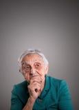 Ηλικιωμένη γυναίκα που σκέφτεται με το διάστημα αντιγράφων ανωτέρω Στοκ φωτογραφίες με δικαίωμα ελεύθερης χρήσης