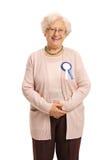 Ηλικιωμένη γυναίκα που φορά μια κορδέλλα βραβείων Στοκ Εικόνες