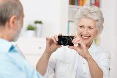 Ηλικιωμένη γυναίκα που φωτογραφίζει το σύζυγό της στοκ εικόνες