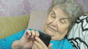 Ηλικιωμένη γυναίκα που χρησιμοποιεί ένα smartphone απόθεμα βίντεο