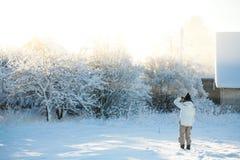 Ηλικιωμένη γυναίκα στα θερμά ενδύματα που εξετάζει το σπίτι προγόνων της σε ένα κρύο και χιονώδες χειμερινό πρωί Στοκ φωτογραφία με δικαίωμα ελεύθερης χρήσης