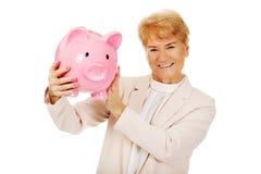 Ηλικιωμένη γυναίκα χαμόγελου που κρατά τη piggy τράπεζα Στοκ Εικόνα