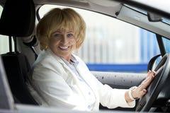 Ηλικιωμένη ευτυχής ηλικιωμένη γυναίκα οδηγών 55-60 έτη στο σακάκι που το εναλλασσόμενο ρεύμα Στοκ Εικόνες