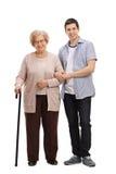 Ηλικιωμένη κυρία με το περπάτημα του καλάμου και του νεαρού άνδρα που βοηθούν την στοκ εικόνα