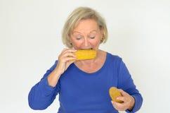 Ηλικιωμένη κυρία που απολαμβάνει το φρέσκο καλαμπόκι στο σπάδικα Στοκ εικόνα με δικαίωμα ελεύθερης χρήσης