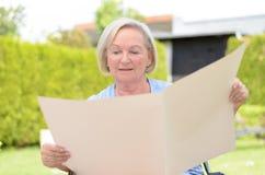 Ηλικιωμένη κυρία που κρατά ένα κενό έγγραφο Στοκ Φωτογραφίες