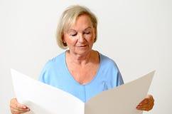 Ηλικιωμένη κυρία που κρατά ένα κενό έγγραφο Στοκ εικόνες με δικαίωμα ελεύθερης χρήσης