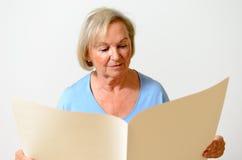 Ηλικιωμένη κυρία που κρατά ένα κενό έγγραφο Στοκ Φωτογραφία