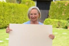Ηλικιωμένη κυρία που παρουσιάζει έναν κενό whiteboard Στοκ Φωτογραφία