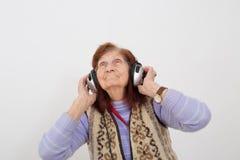 Ηλικιωμένη μουσική γυναικείου ακούσματος με τα ακουστικά Στοκ φωτογραφία με δικαίωμα ελεύθερης χρήσης