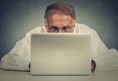Ηλικιωμένη συνεδρίαση ατόμων στον πίνακα που λειτουργεί στο φορητό προσωπικό υπολογιστή Στοκ Εικόνες