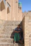 Ηλικιωμένη συνεδρίαση γυναικών στη σκιά στα σκαλοπάτια στοκ εικόνα