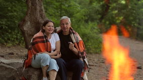 Ηλικιωμένη συνεδρίαση ζευγών γύρω από μια πυρά προσκόπων στα ξύλα φιλμ μικρού μήκους