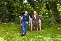 Ηλικιωμένη συνεδρίαση ζευγών χέρι-χέρι στοκ εικόνα