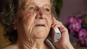 Ηλικιωμένη συνταξιούχος γυναίκα που μιλά στο τηλέφωνο φιλμ μικρού μήκους