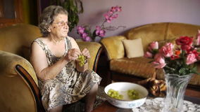 Ηλικιωμένη συνταξιούχος γυναίκα που τρώει τα σταφύλια φιλμ μικρού μήκους
