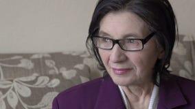 Ηλικιωμένη χαριτωμένη γυναίκα με τα γυαλιά που φαίνεται έξω παράθυρο Ευτυχής φιλμ μικρού μήκους