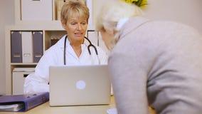 Ηλικιωμένος γιατρός συνεδρίασης των γυναικών στην αρχή απόθεμα βίντεο