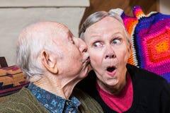 Ηλικιωμένος κύριος που φιλά την ηλικιωμένη γυναίκα στο μάγουλο Στοκ εικόνες με δικαίωμα ελεύθερης χρήσης