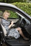 Ηλικιωμένος οδηγός γυναικών που στερεώνει τη μόνη ζώνη σε ένα αυτοκίνητο Στοκ εικόνα με δικαίωμα ελεύθερης χρήσης