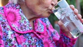 Ηλικιωμένος παλαιότερος χεριών κρατά τις ταμπλέτες και πίνει το νερό φιλμ μικρού μήκους