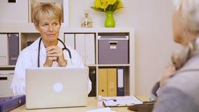 Ηλικιωμένος υπομονετικός συμβουλευτικός θηλυκός γιατρός απόθεμα βίντεο